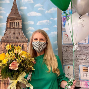 woman poses with balloons and flowers