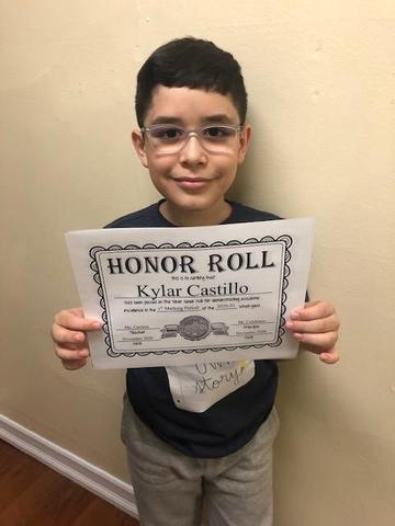 Kylar holding honor roll certificate