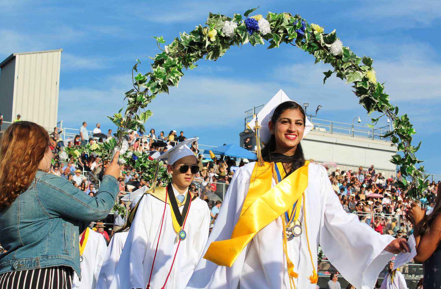 VHS graduate walking through floral arches.