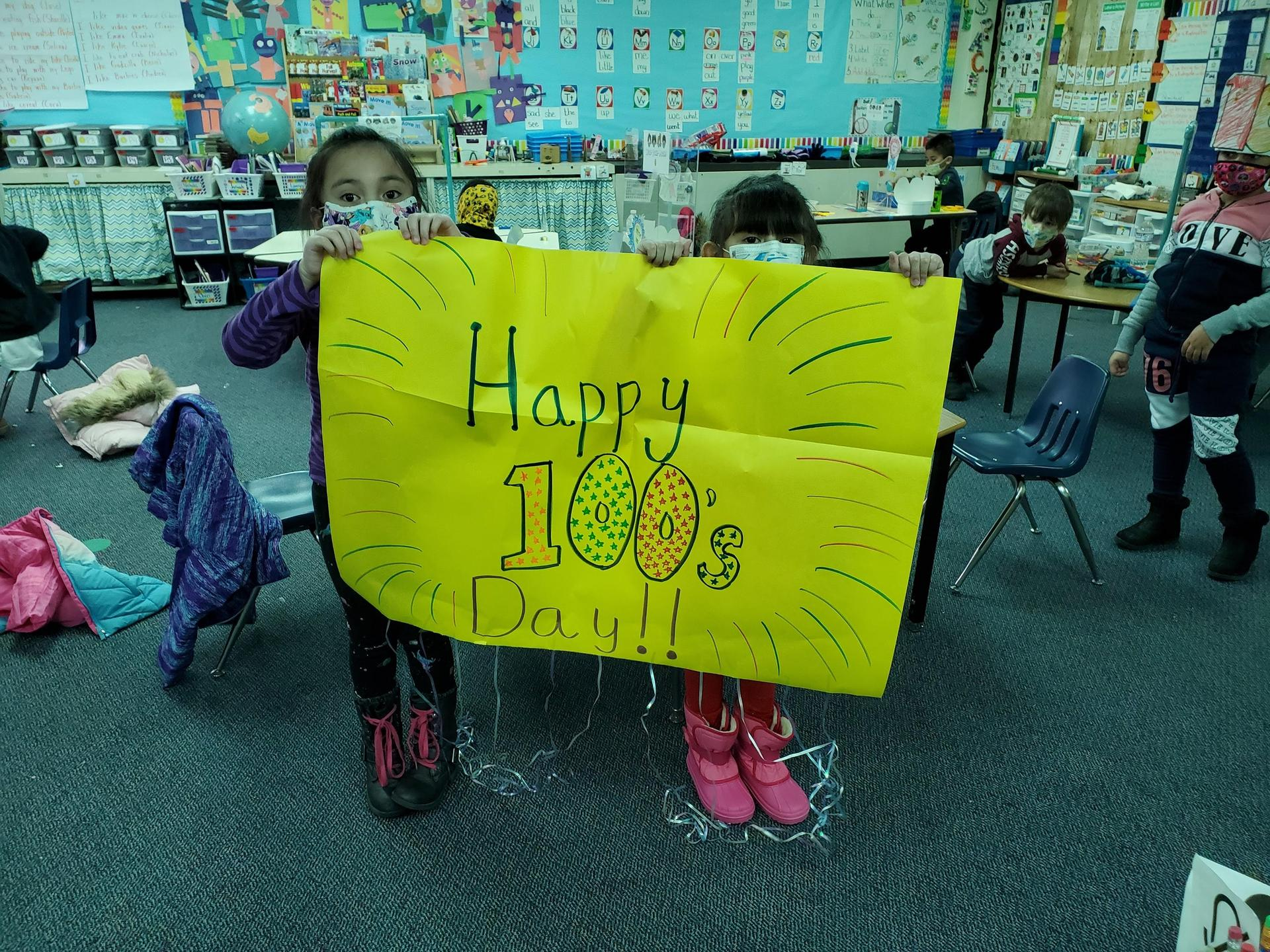 students holding 100s day sign