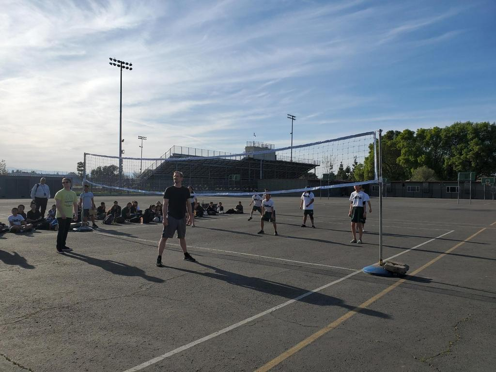 A photo of a volleyball court where teachers are playing students in volleyball.