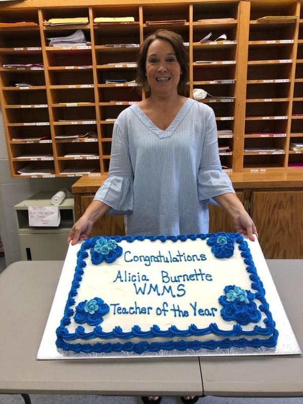 Mrs Burnette holding cake.