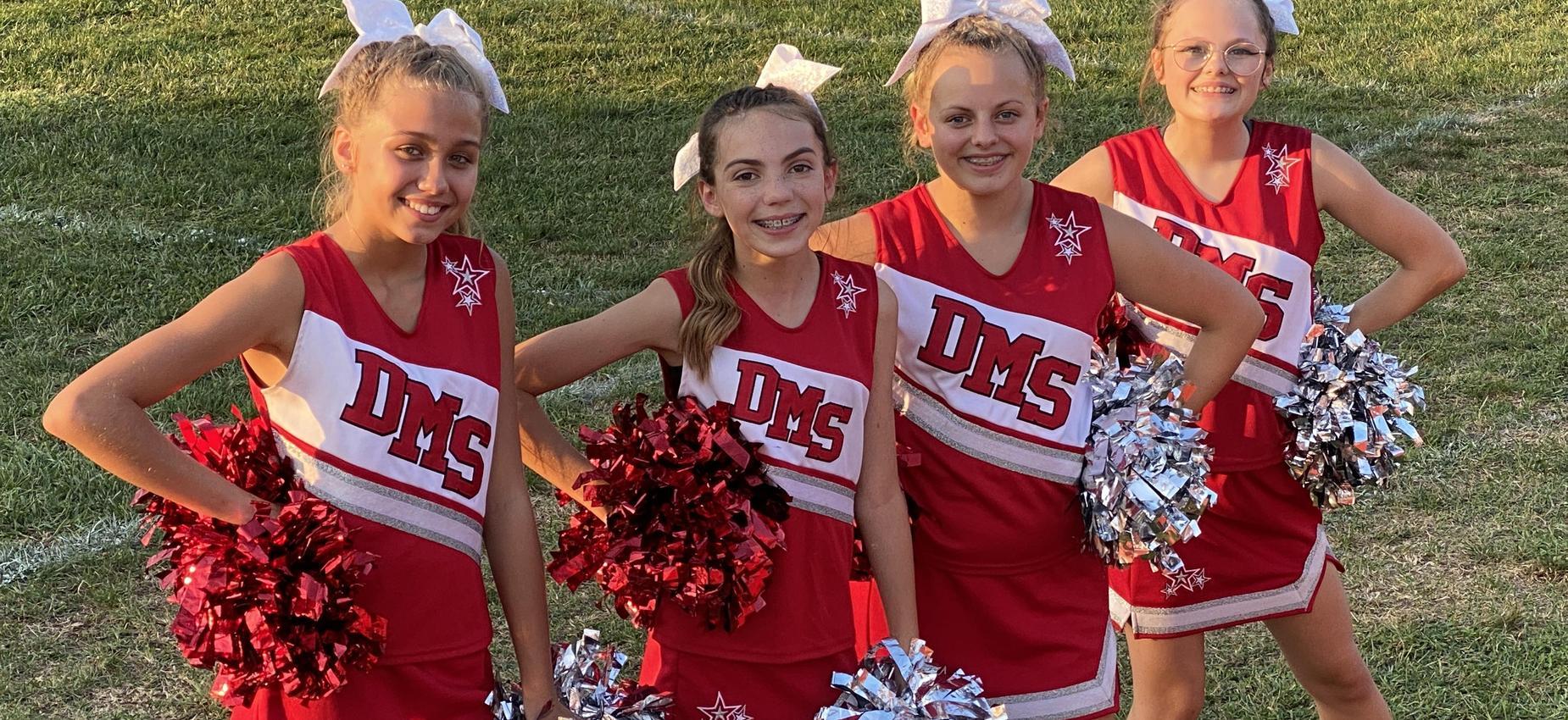 Four cheerleaders pose on a football field.