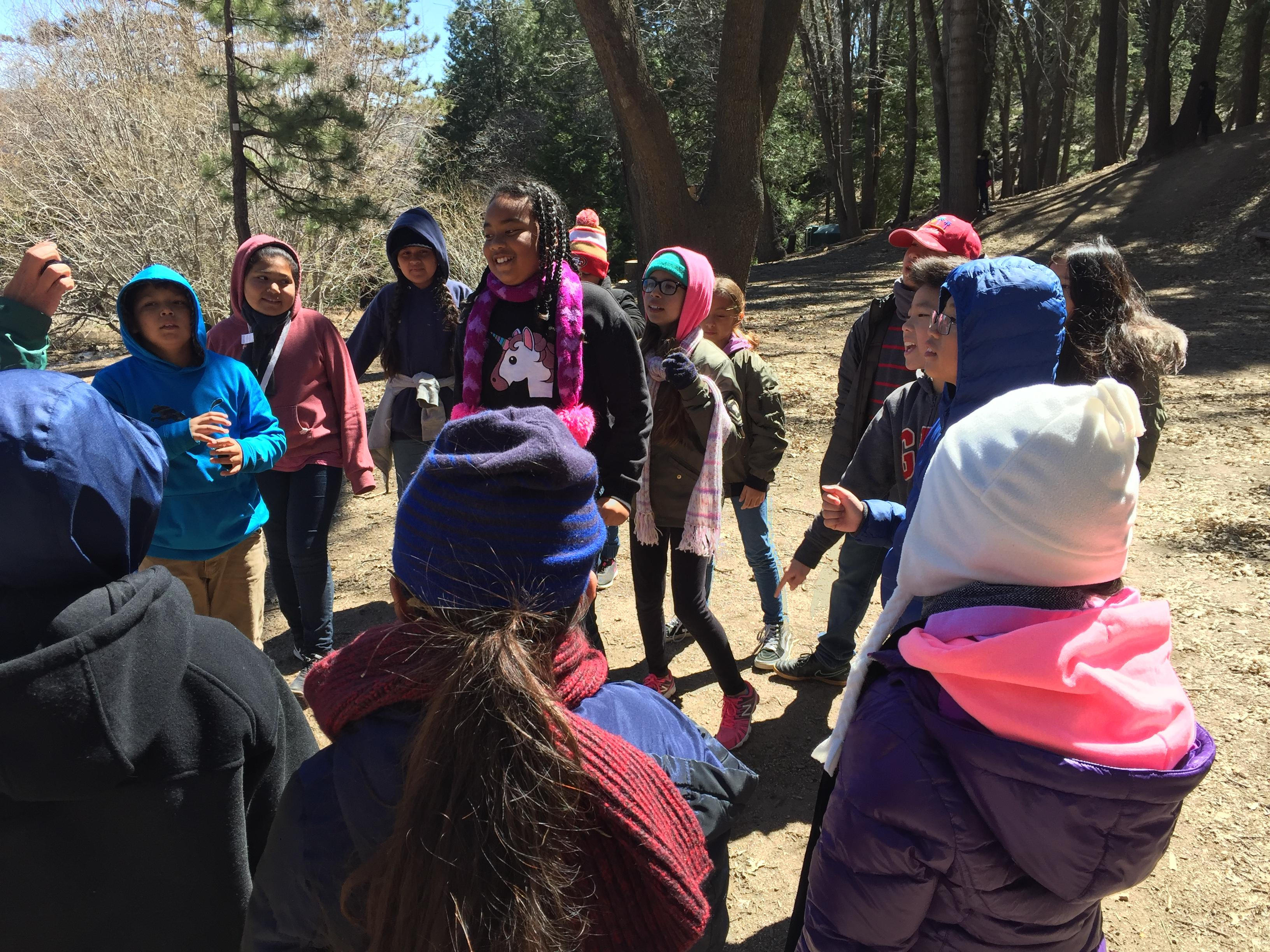 Several students at outdoor camp, playing a game in their winter clothes.
