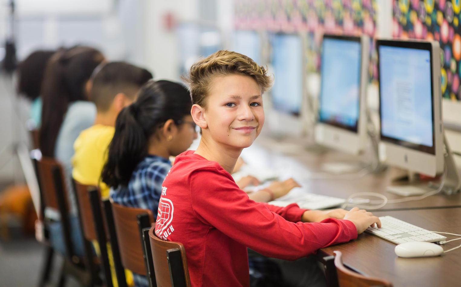 Middle school student at computer in library.