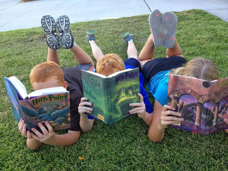 Kids laying the grass, reading books