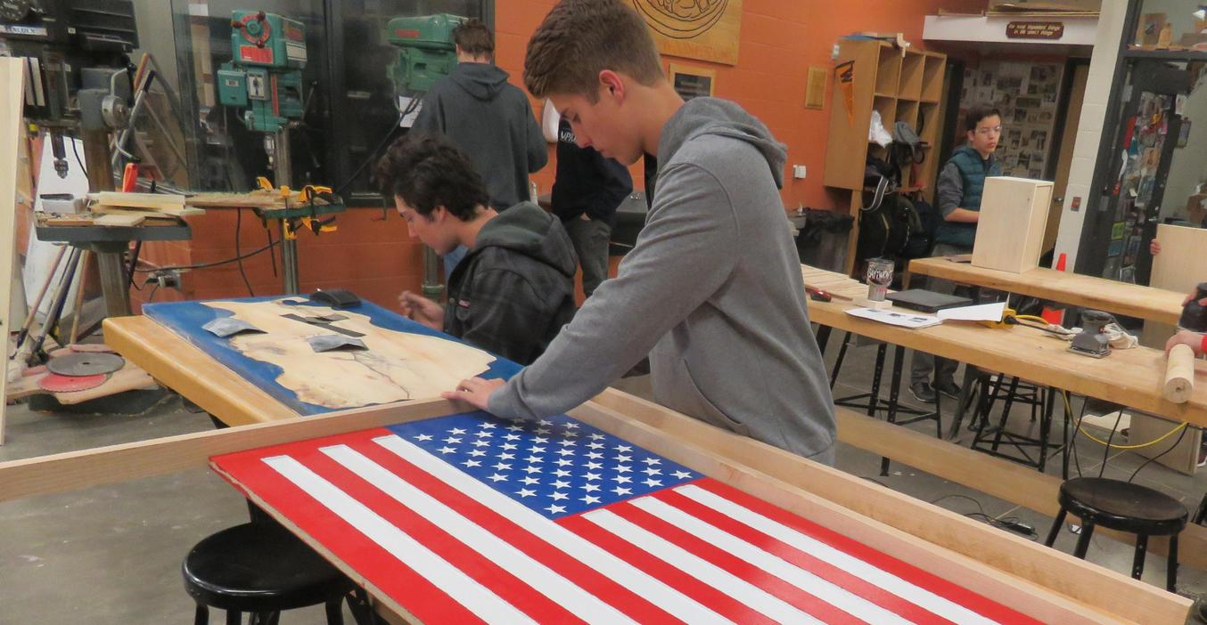 A woods student works to finish up a table.