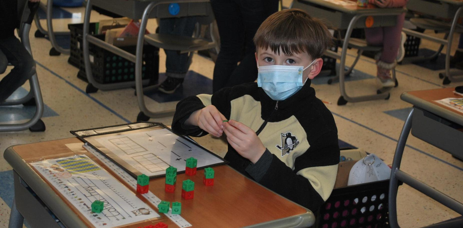 boy doing math with manipulatives