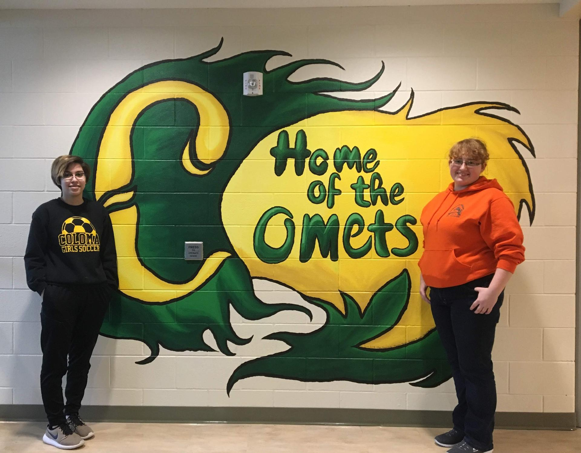 Art Club students; Haileigh and Brenna stand proudly by a mural they helped to paint for the school's front entrance in Summer 2018.