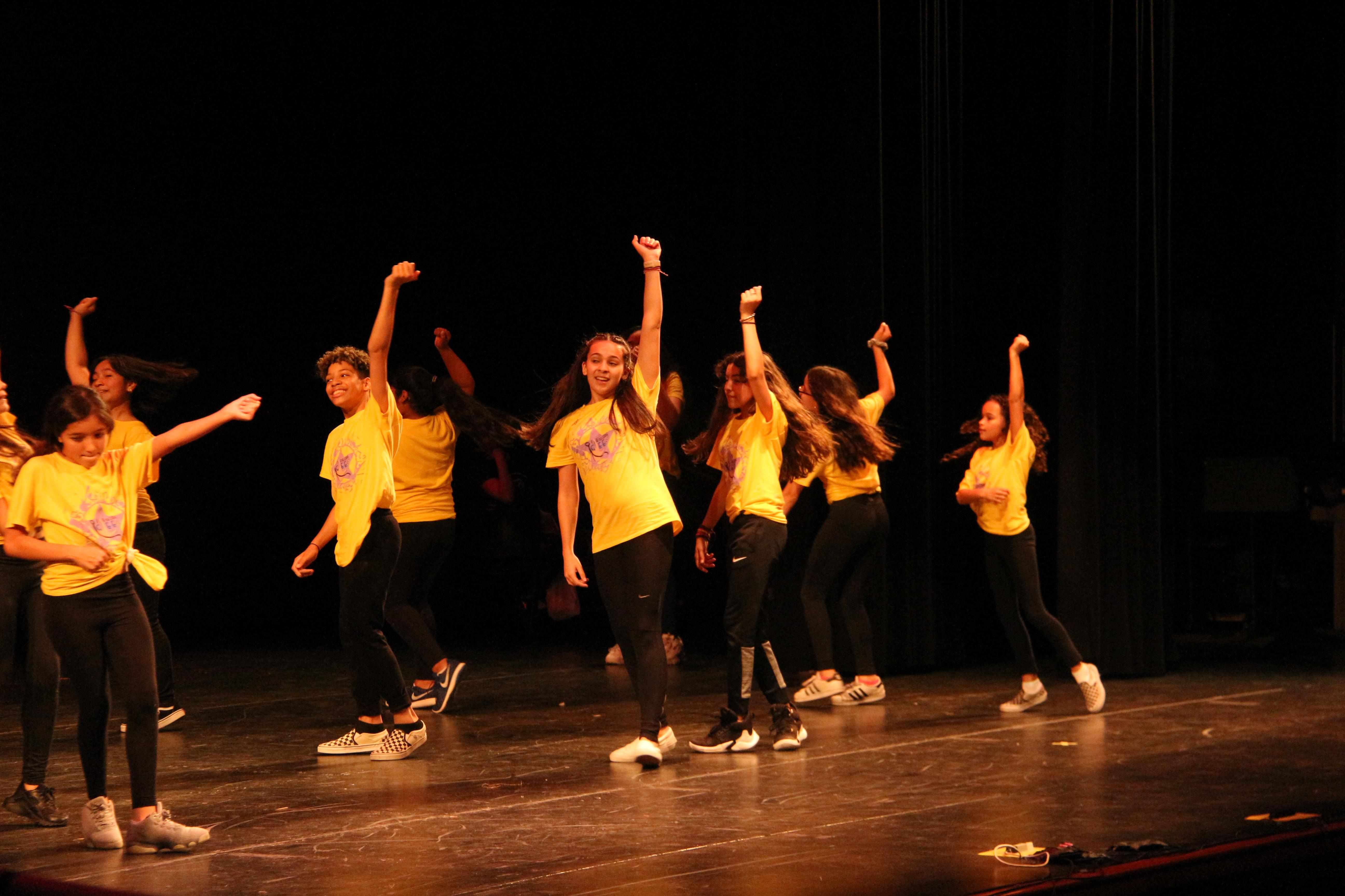 middle school girls wearing yellow t-shirts dancing together