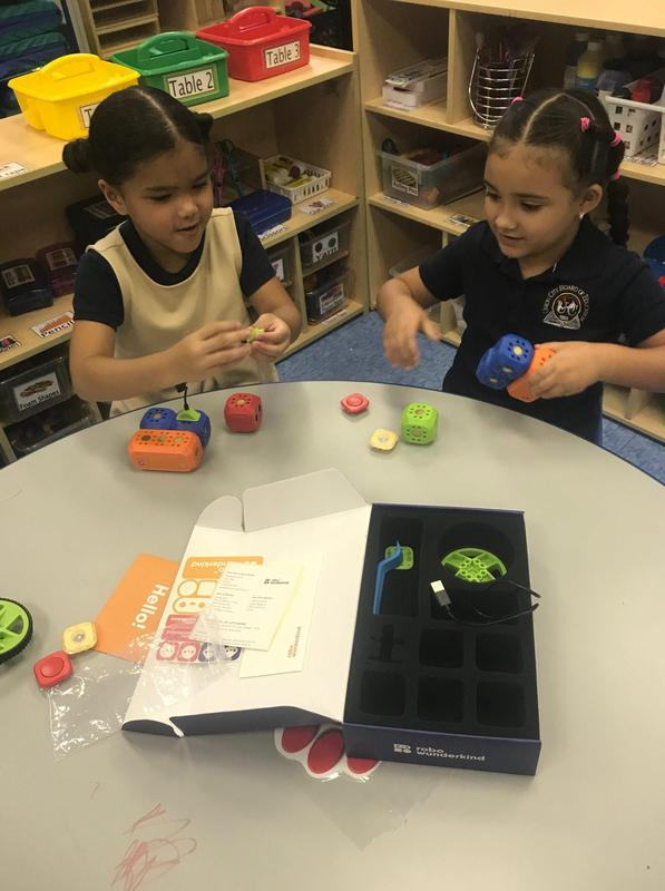 two girls seated at a table working with a robo wunderkind kit putting together cubes to create a robot