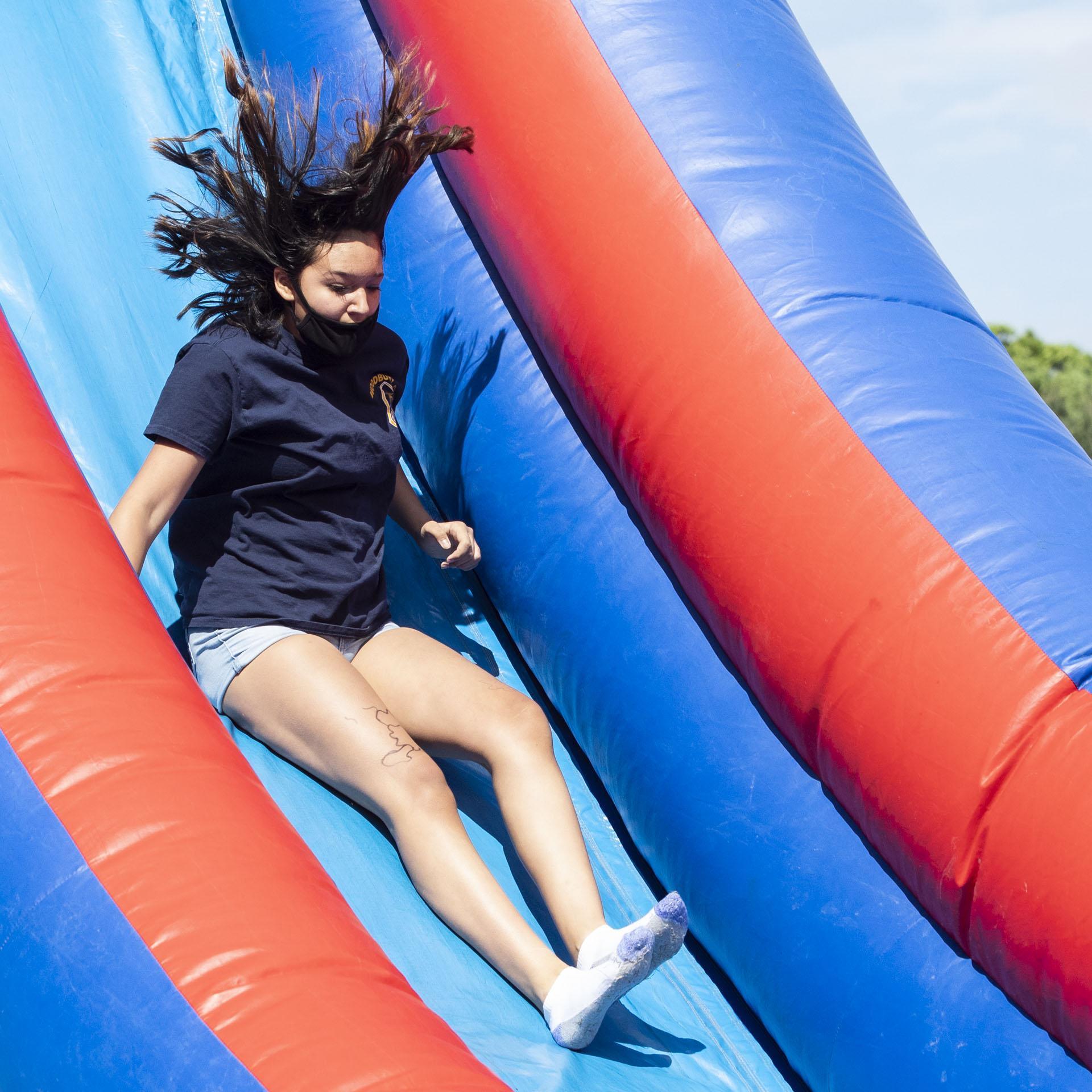 Student sliding down bouncy slide