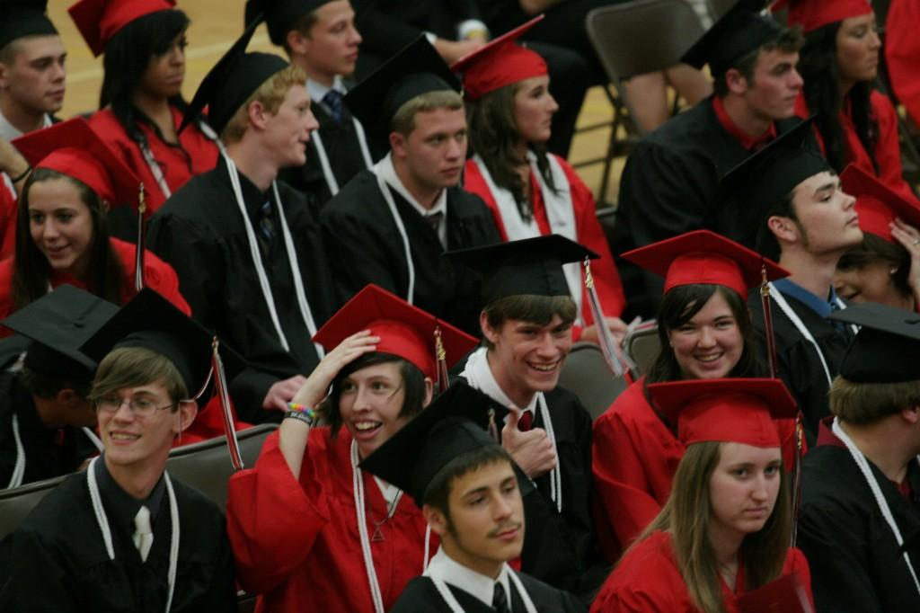 Graduates smiling and giving the thumbs up signal