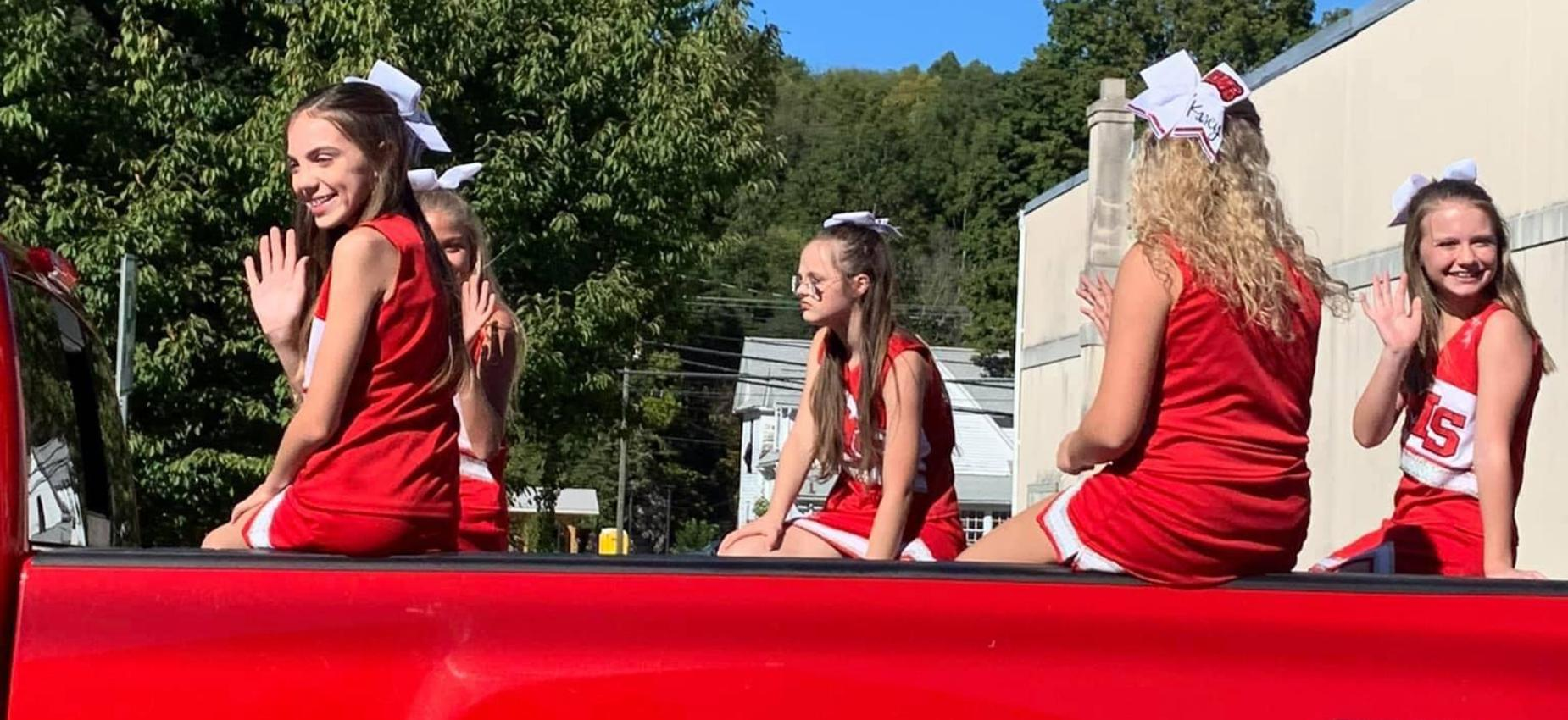 A group of cheerleaders ride in the back of a truck.