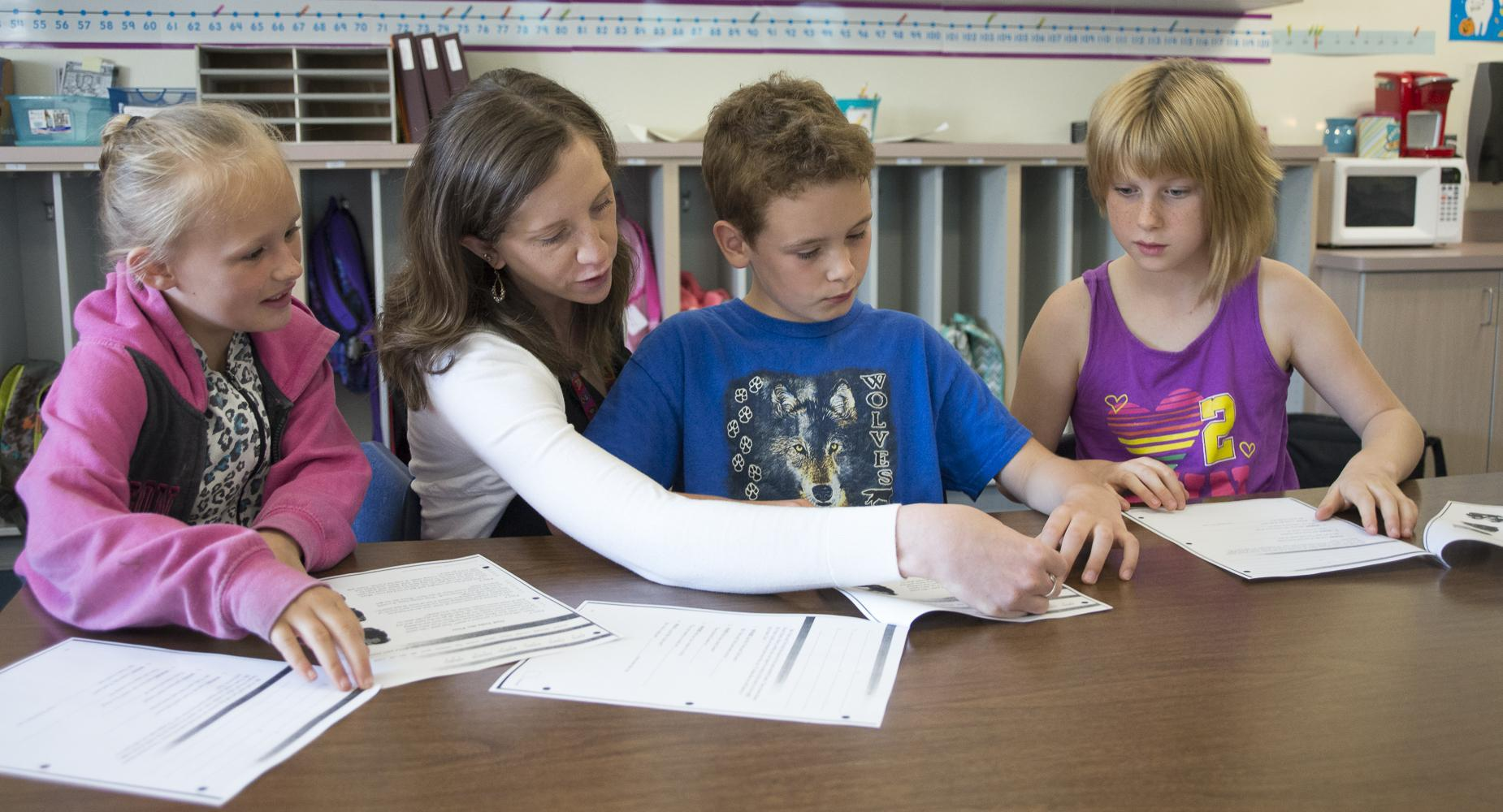 Teacher helps three children with a worksheet