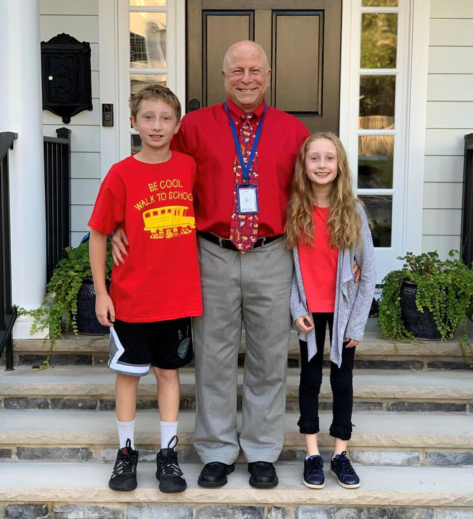 Photo of Washington principal Dr. Andrew Perry with two students on Walk To School Day.