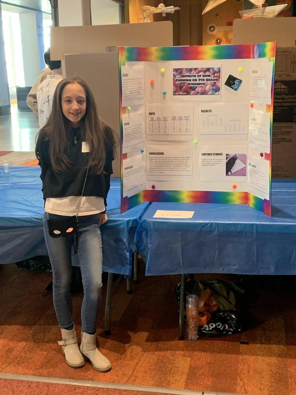 UHMS student in front of her research board