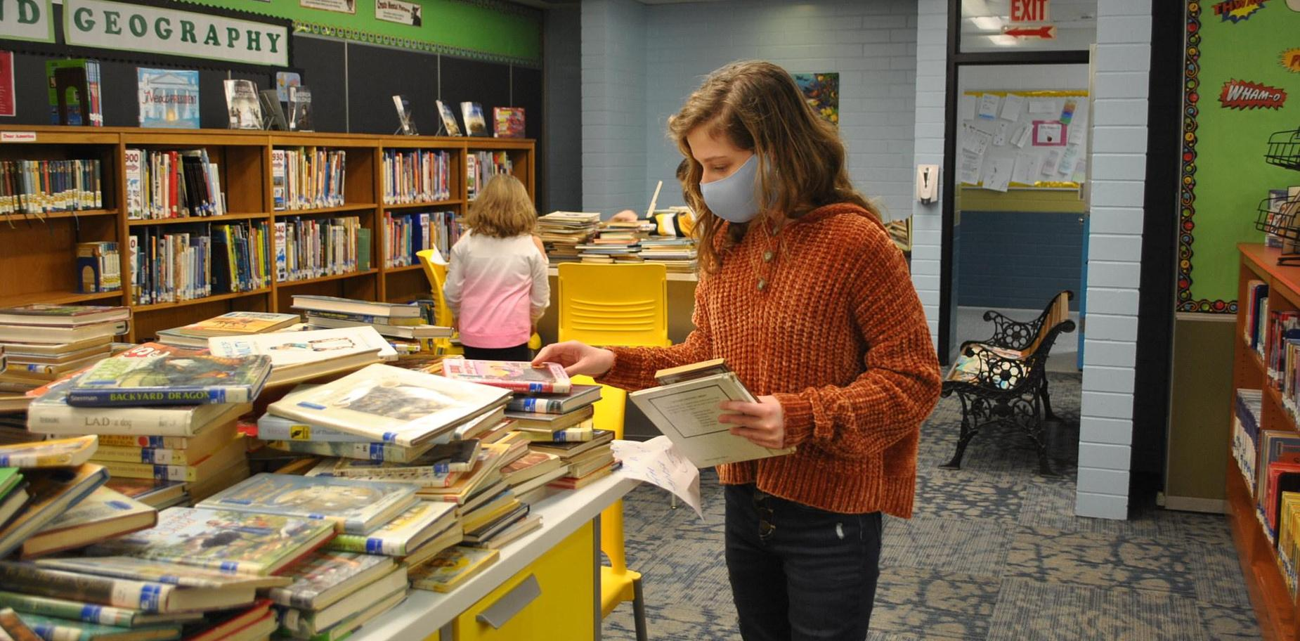student selecting a library book
