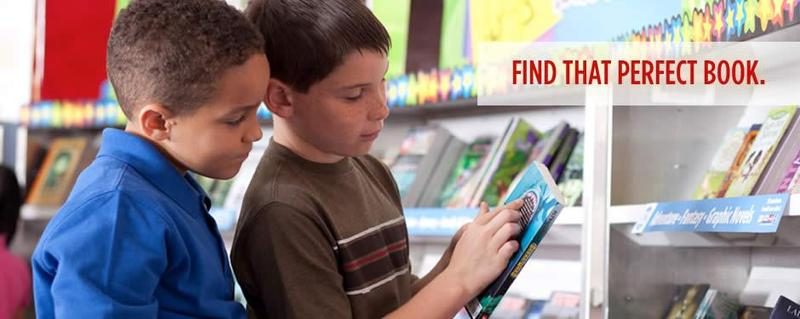 Two boys are shopping for a book to buy at the book fair.