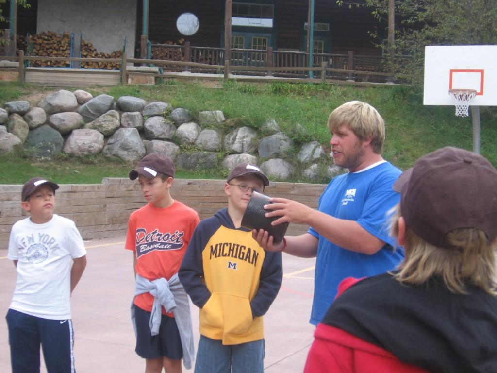 camp counselor teaches kids a game