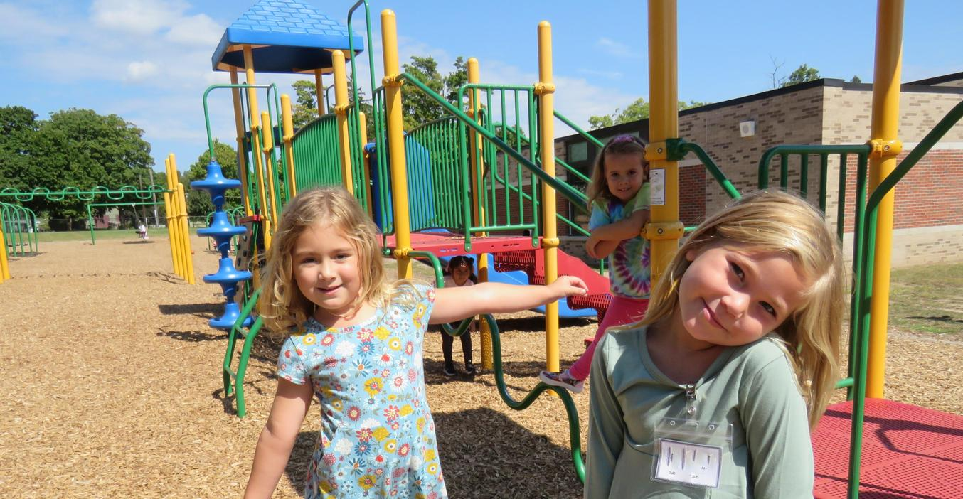 Three girls play on the playground together.