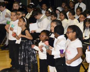 A group of elementary students performing a carol
