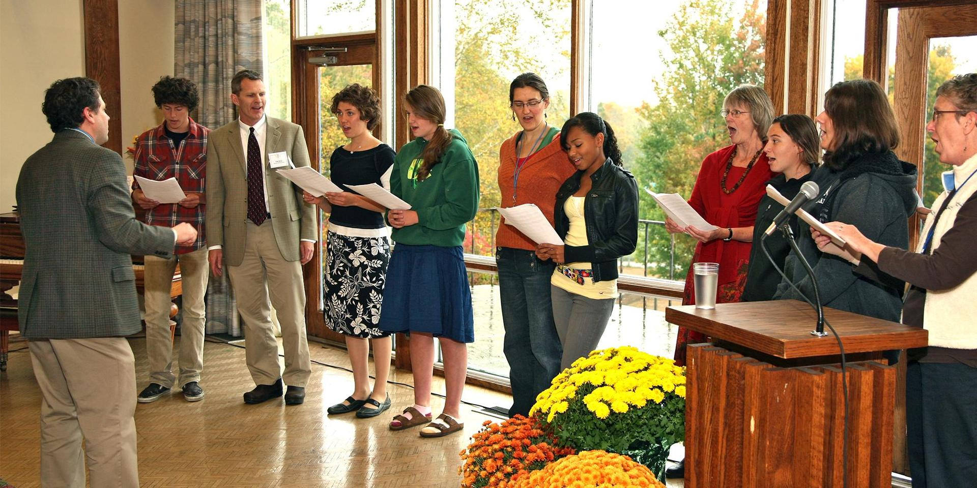 A group of alumnae/i singing.