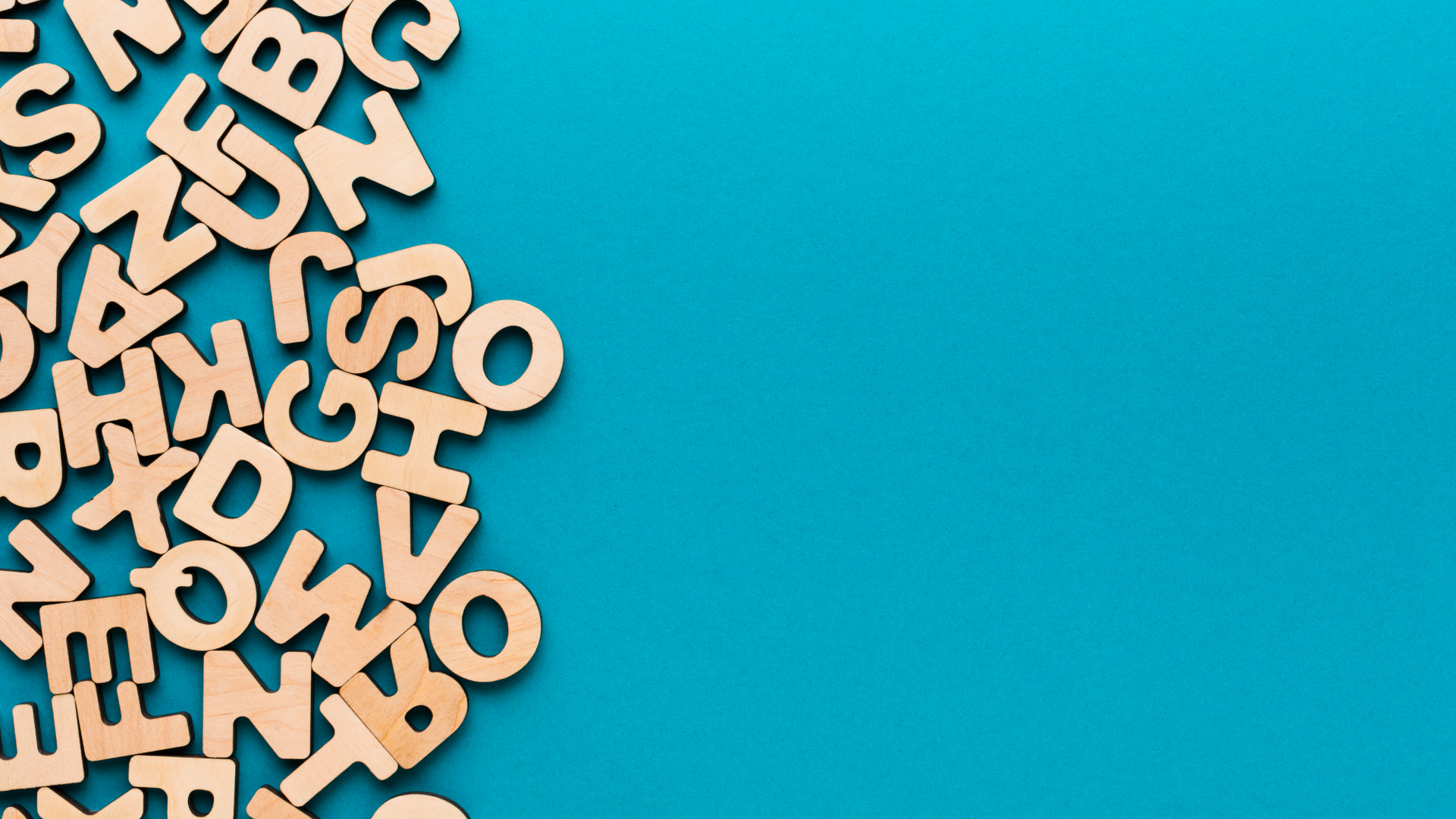 turquoise background with random wooden letters