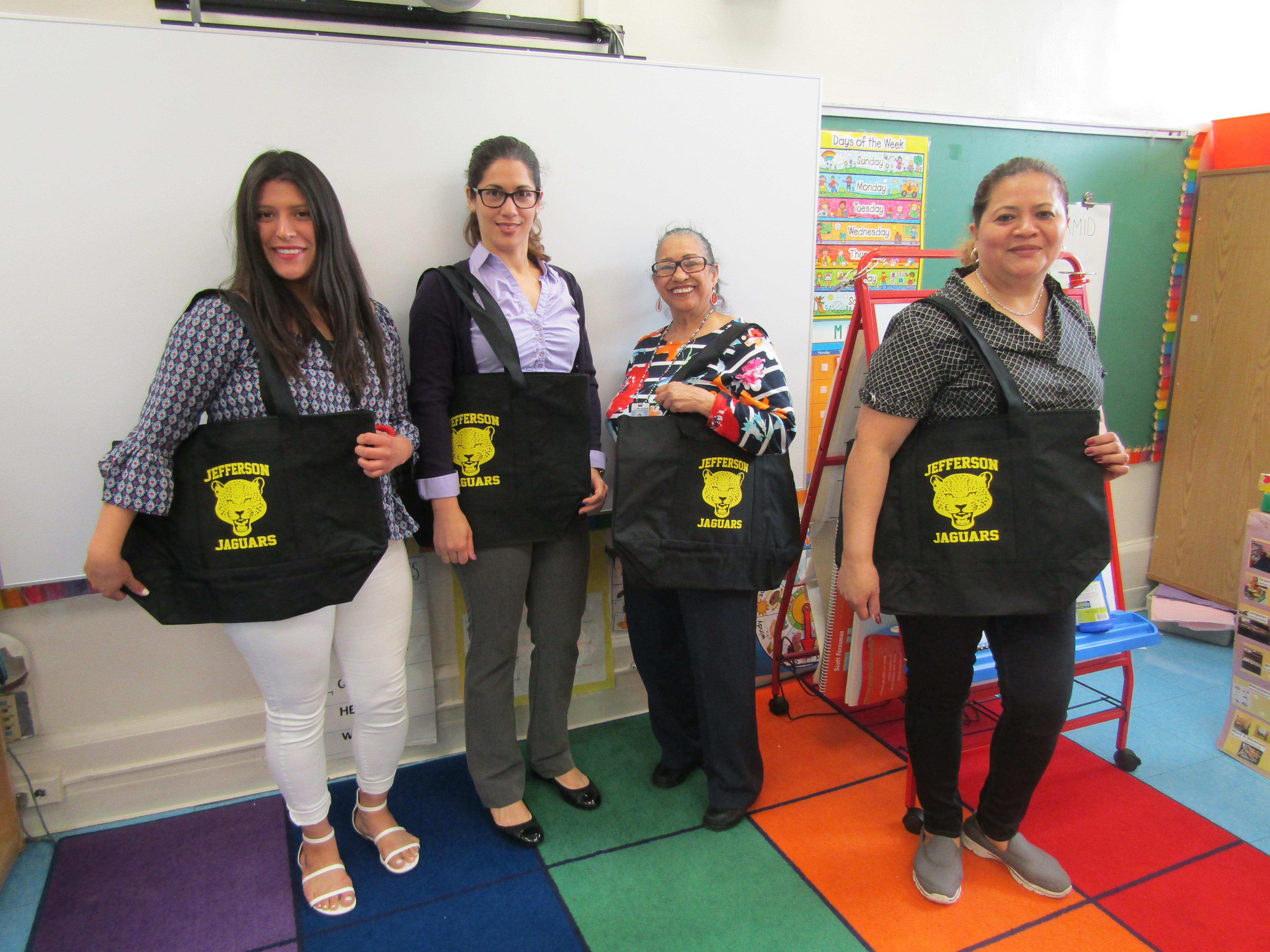 group 3 of teachers showing off their totes
