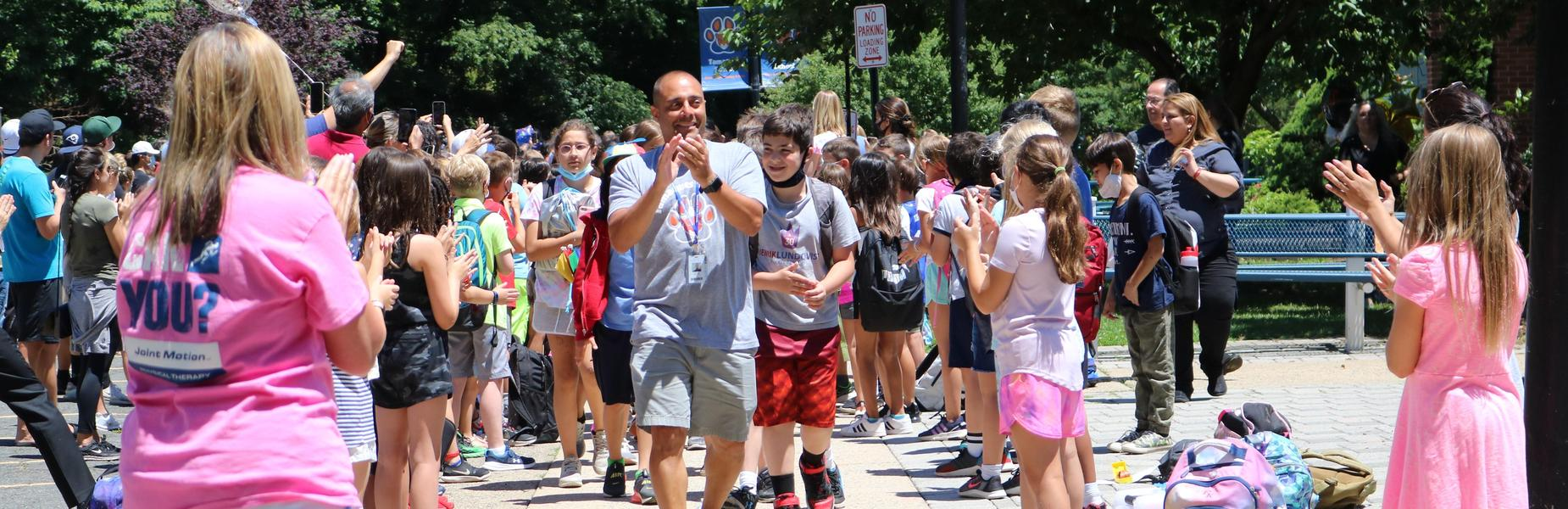 Photo of Tamaques 5th grade teacher leading his students during Grade 5 clapout, as families and other students/teachers applaud the 5th graders.