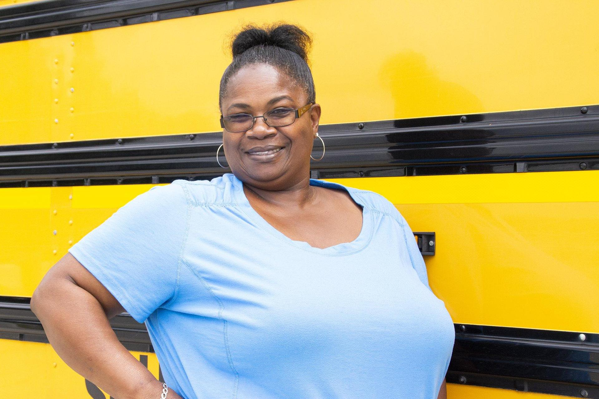 woman standing beside school bus