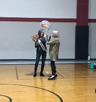 Sarah accepting her flowers and balloon