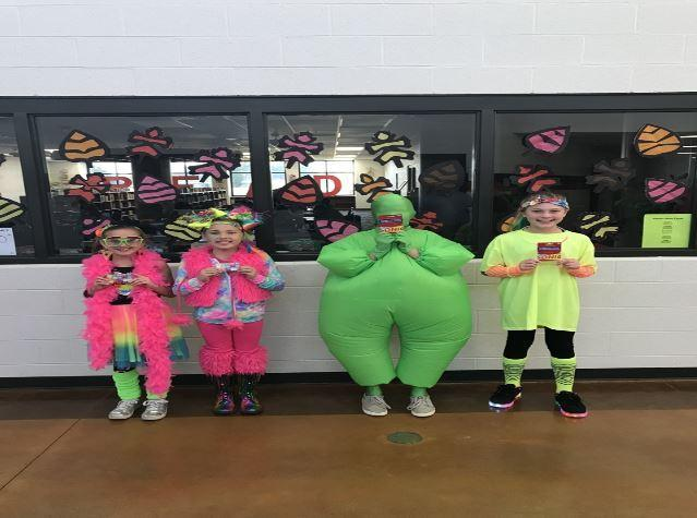 4 middle school students dressed in neon colored clothing