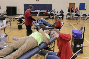 Students give a thumbs up while giving blood.
