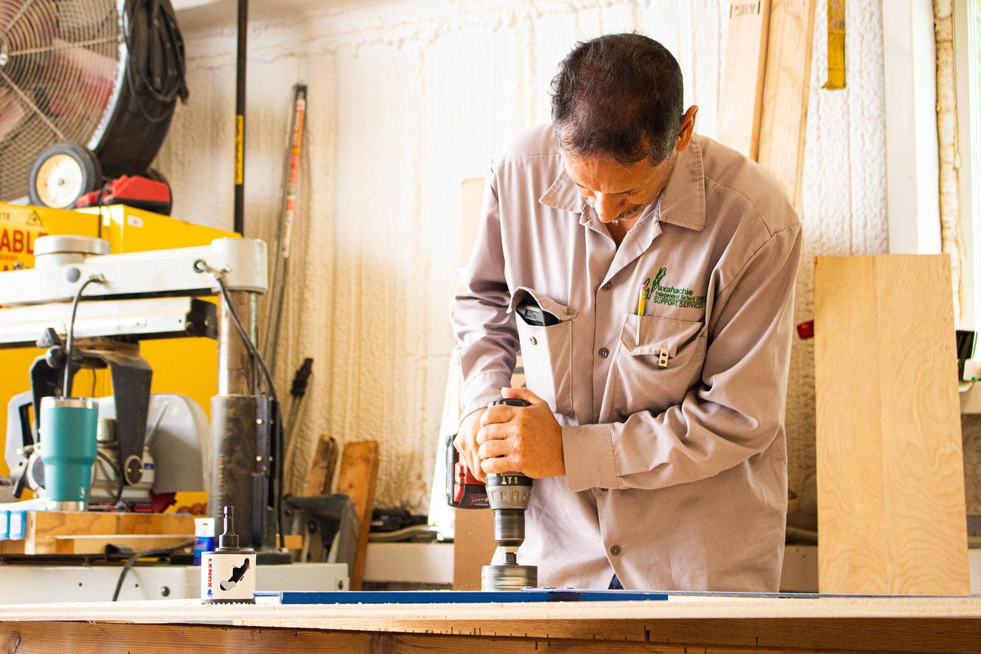 man drilling wood