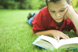 boy reading book on the grass