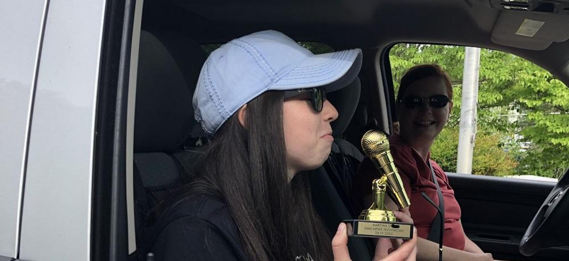 A student holds a trophy in a car.
