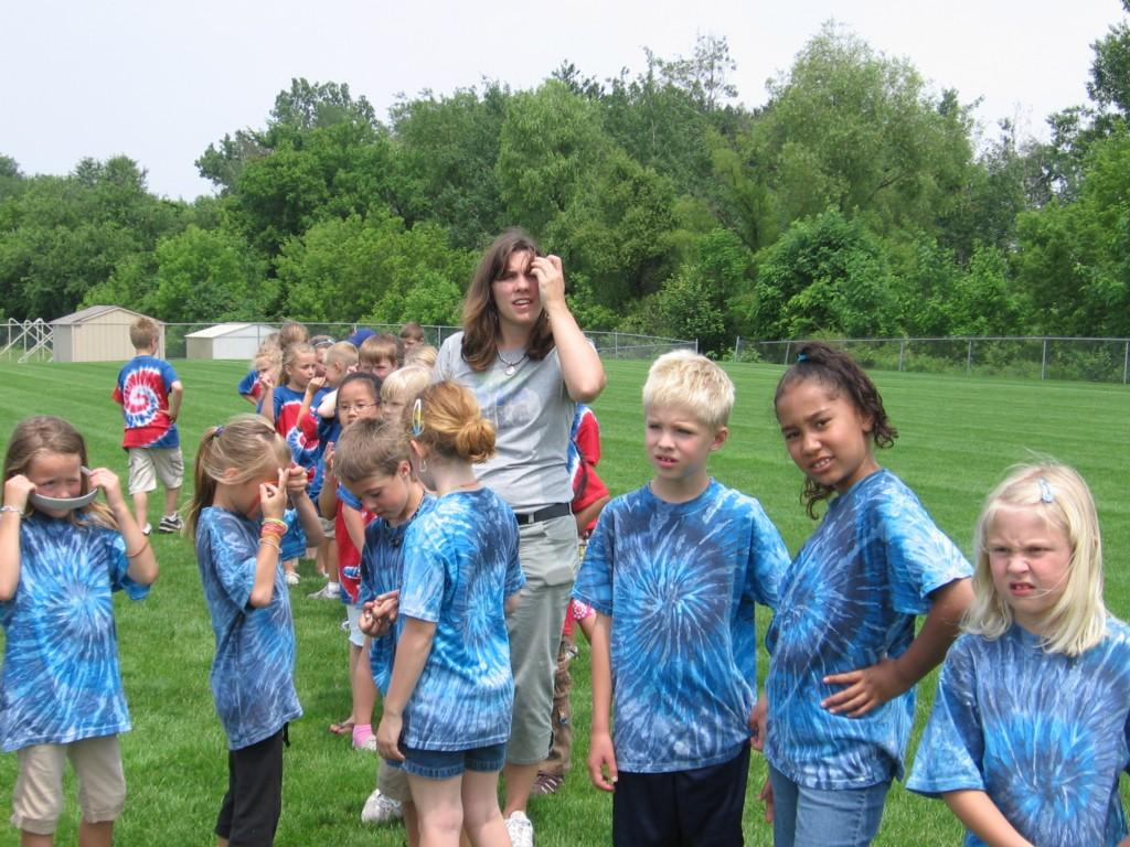 students stand around outside in tie dye shirts