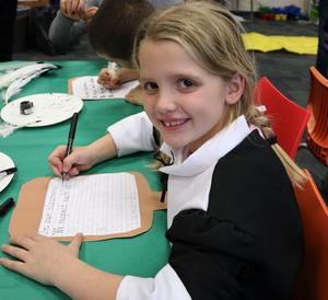 2nd grader, dressed in colonial era dress, tries her hand at calligraphy during Colonial Days at Wilson School.
