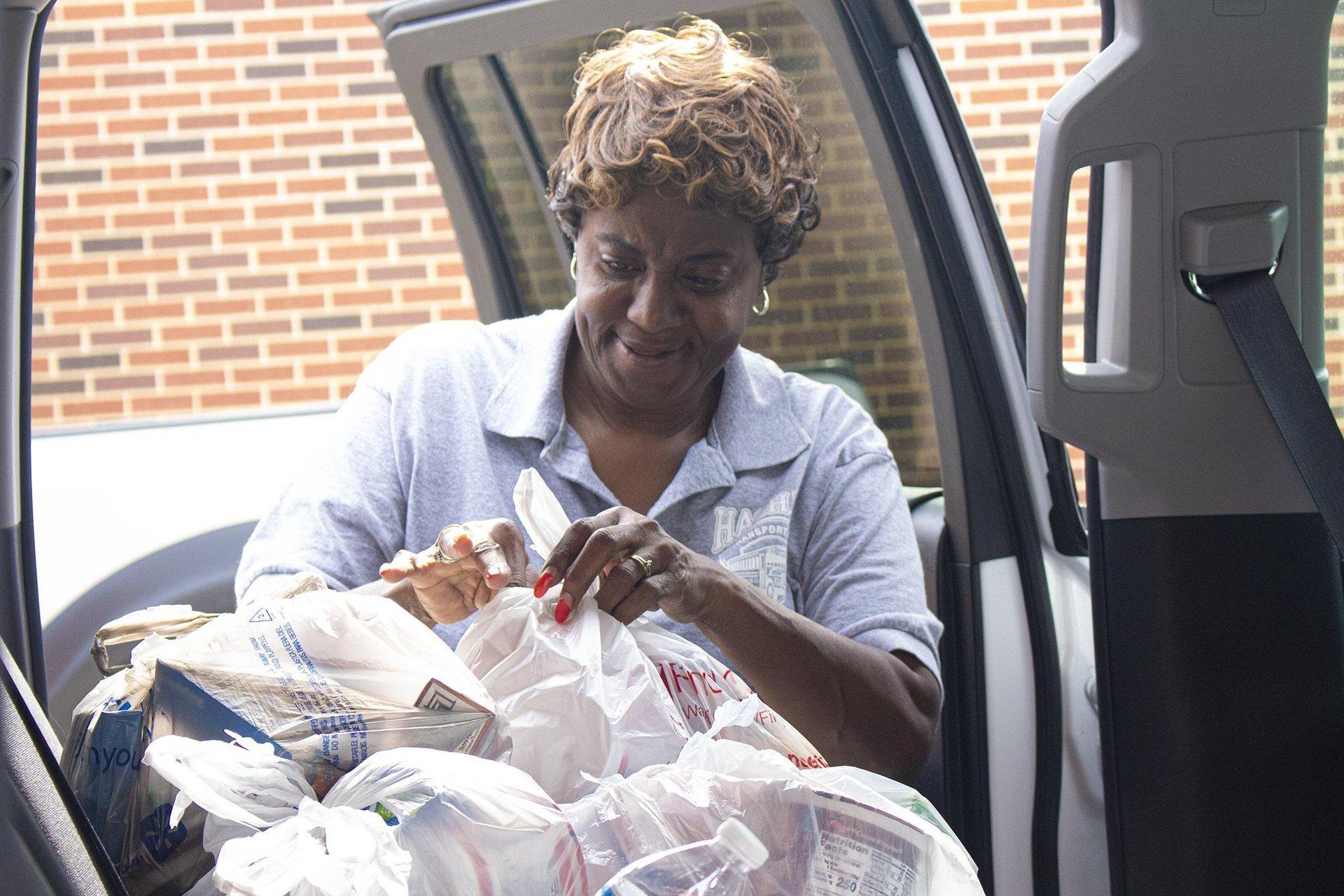 woman in back of van unloading groceries