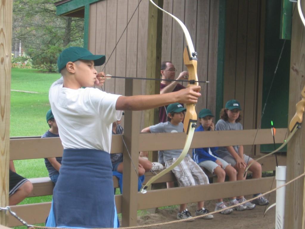 boy aims with bow and arrow