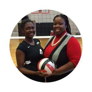 Student and volleyball coach pictured in front of the net holding a volleyball.