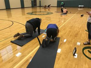 Students stretch in the gym as part of maintaining physical activity.