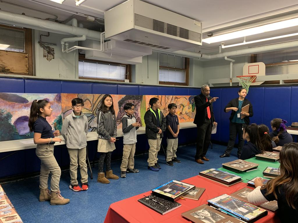 several students standing next to Artist Brooks and the Art teacher in the front the art work