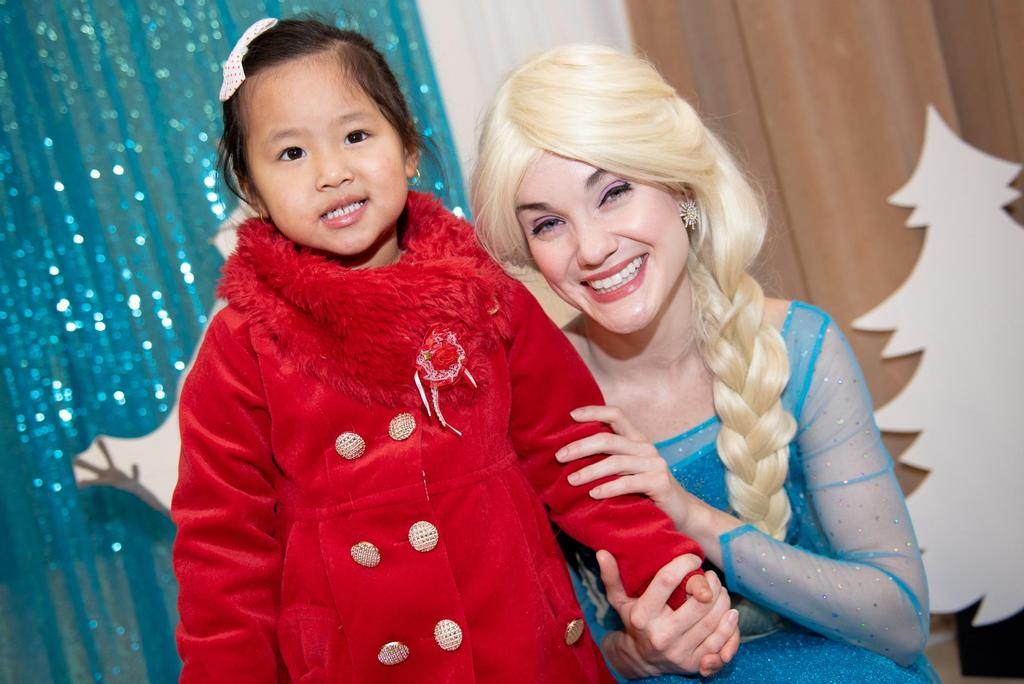 """Elsa from """"Frozen"""" holds hands with a young student"""