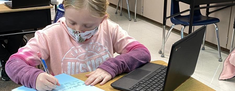 Student working diligently with her laptop while writing on a piece of paper at her desk.