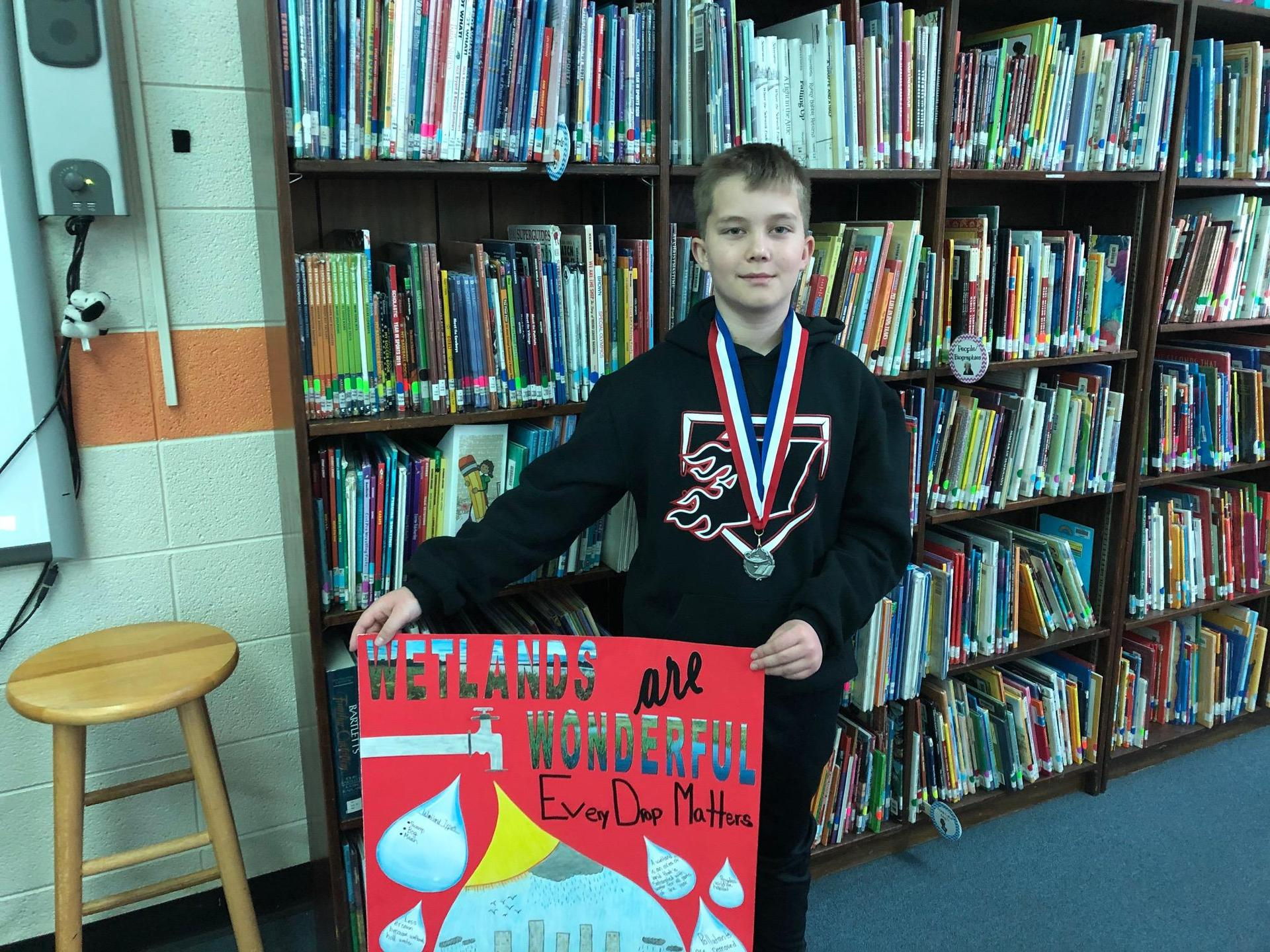 Hayden with poster and medal