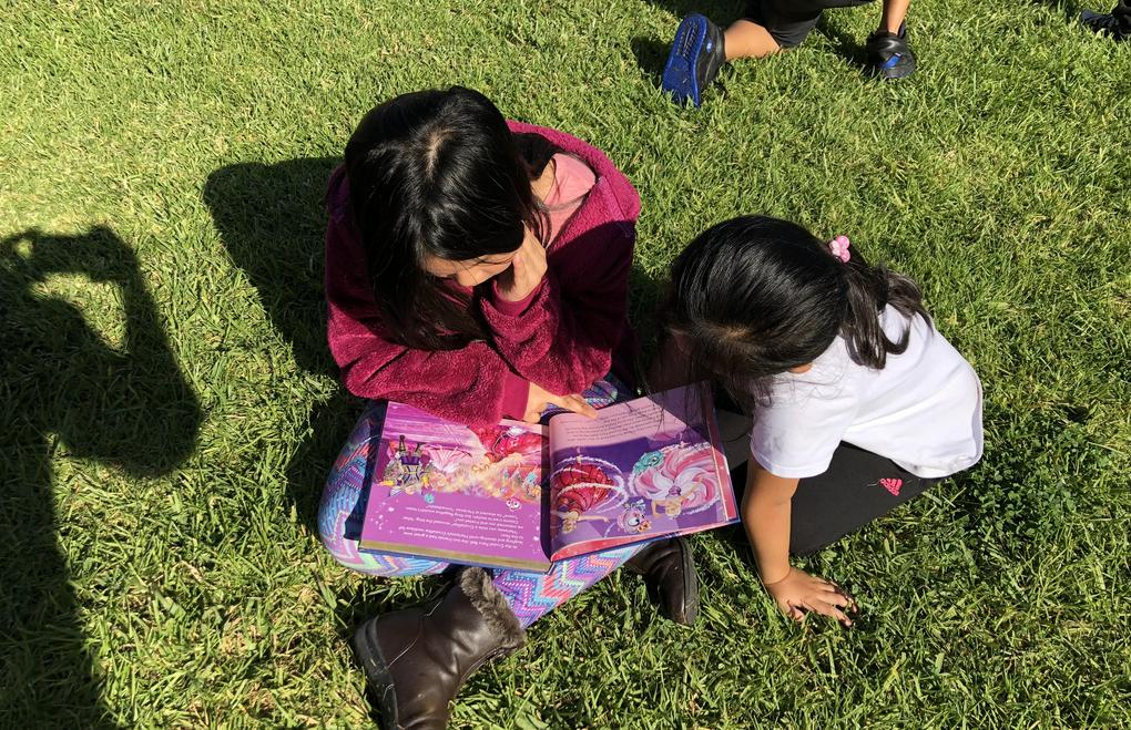 Two students sit together reading a book.