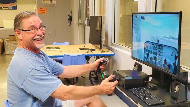 Science and STEM Pilot program teacher John Kopaczewski tests a flight plan from LaGuardia Airport to the Statue of Liberty on one of 10 new flight simulators. Beatty Middle School students will take the flight as part of a new STEM Pilot program.