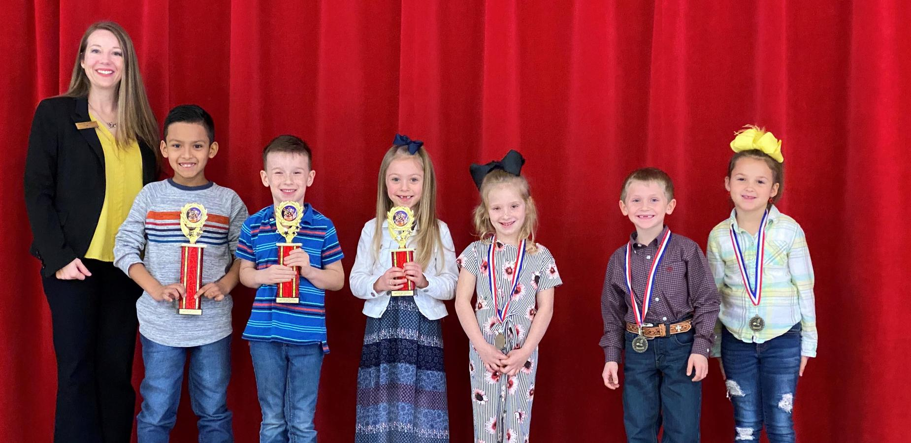 Mrs. Fowler pictured with spelling bee winners 1st through 6th places with their trophies and medals